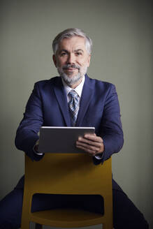 Portrait of mature businessman sitting on a chair holding tablet - RBF07651
