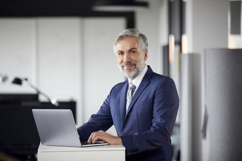 Portrait of mature businessman using laptop in office - RBF07663