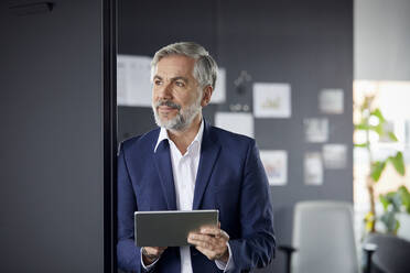 Mature businessman using tablet in office - RBF07675