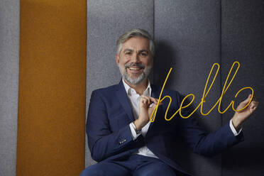 Portrait of smiling mature businessman sitting on couch in office holding hello sign - RBF07678