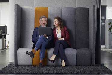 Happy businesswoman and businessman sitting on couch in office sharing laptop - RBF07681
