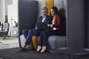 Businesswoman and businessman sitting on couch in office sharing laptop - RBF07684