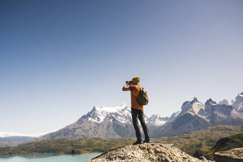 Hiker in mountainscape looking through binoculars at Lago Pehoe in Torres del Paine National Park, Patagonia, Chile - UUF20235
