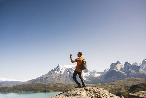 Hiker cheering in mountainscape at Lago Pehoe in Torres del Paine National Park, Patagonia, Chile - UUF20238