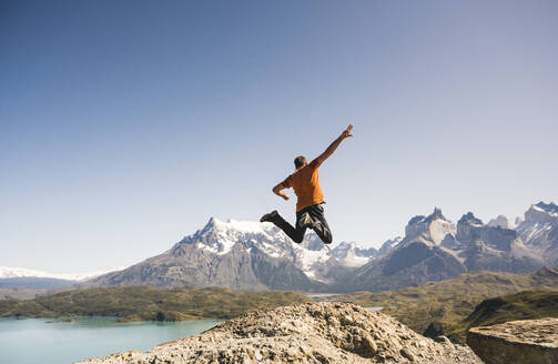 Hiker jumping in mountainscape at Lago Pehoe in Torres del Paine National Park, Patagonia, Chile - UUF20241