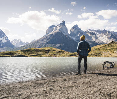 Hiker in mountainscape at lakeside in Torres del Paine National Park, Patagonia, Chile - UUF20247