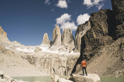 Hiker in mountainscape at lakeside at Mirador Las Torres in Torres del Paine National Park, Patagonia, Chile - UUF20268