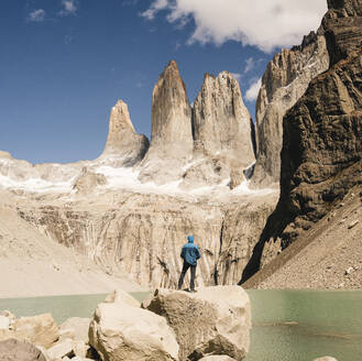 Hiker in mountainscape at lakeside at Mirador Las Torres in Torres del Paine National Park, Patagonia, Chile - UUF20271