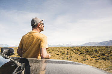 Rear view of man at car in remote landscape in Patagonia, Argentina - UUF20274