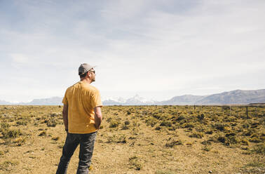 Rear view of man standing in remote landscape in Patagonia, Argentina - UUF20280