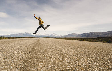 Man jumping on a road in remote landscape in Patagonia, Argentina - UUF20286