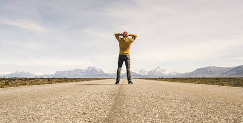 Man standing on a road in remote landscape in Patagonia, Argentina - UUF20289