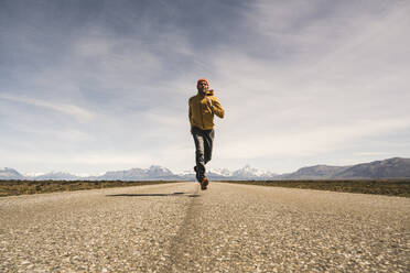 Man running on a road in remote landscape in Patagonia, Argentina - UUF20292