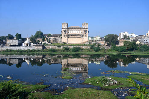 The 18th century Naulakha Palace facade reflected in the still waters of the Gondal River, Gondal, Gujarat, India, Asia - RHPLF14967