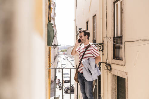 Young man on the phone in the city, Lisbon, Portugal - UUF20315