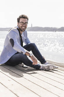 Portrait of happy young man sitting on the waterfront - UUF20339