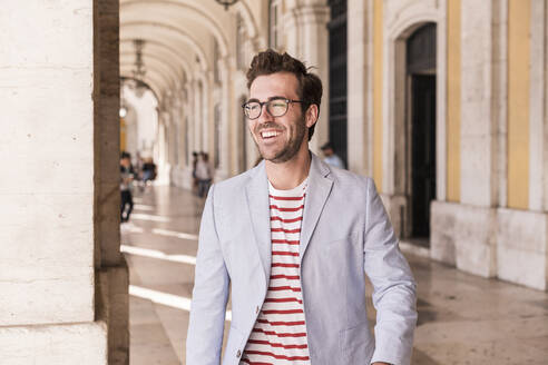 Piortrait of happy young man in the city, Lisbon, Portugal - UUF20342