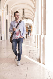Smiling young man with smartphone in the city, Lisbon, Portugal - UUF20348