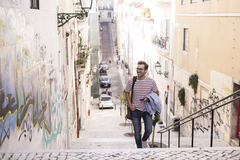 Young man walking up stairs in the city, Lisbon, Portugal - UUF20351