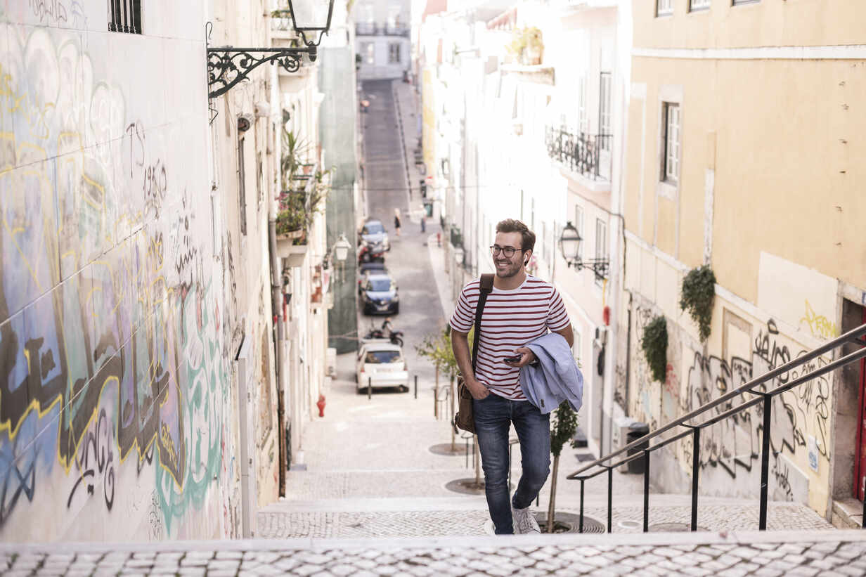 Young man walking up stairs in the city, Lisbon, Portugal - UUF20351 - Uwe Umstätter/Westend61