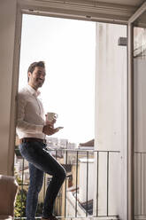 Young man with cell phone and coffee cup on a balcony - UUF20354
