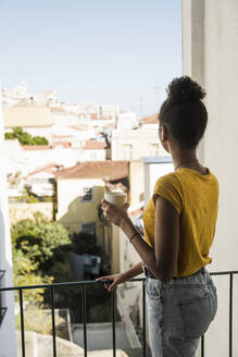 Young woman with coffee cup on a balcony - UUF20363