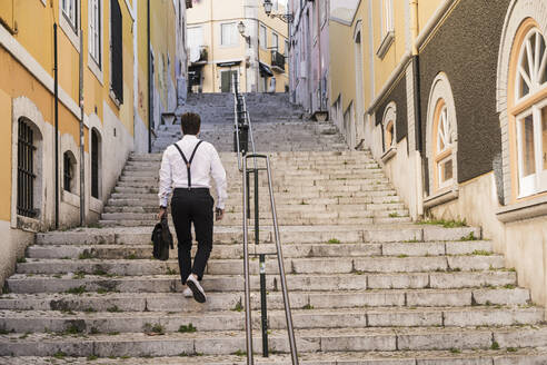 Rear view of young man walking up stairs in the old town, Lisbon, Portugal - UUF20366