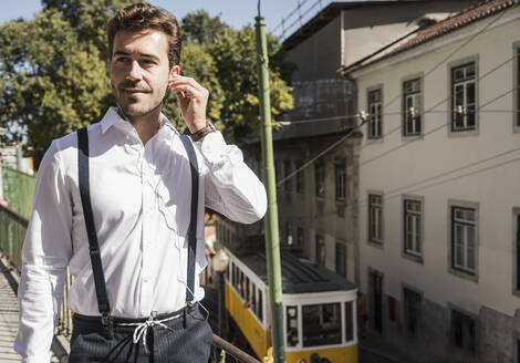 Young man with earbuds in the city, Lisbon, Portugal - UUF20372