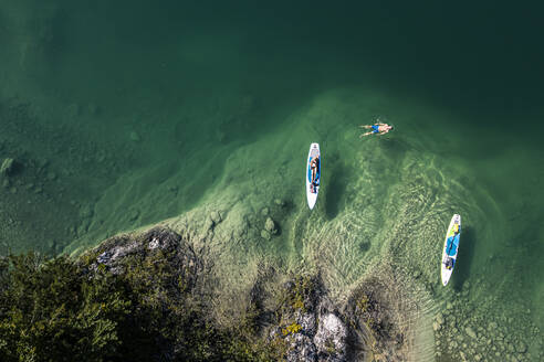 Germany, Bavaria, Aerial view of two paddleboarders relaxing on green shore of Lake Walchen - WFF00388