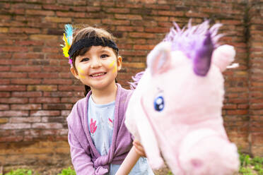 Portrait of girl with braids and feather headdress riding a pink unicorn - GEMF03639