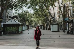 Full length portrait of woman standing on empty footpath in city, Barcelona, Spain - GMLF00179