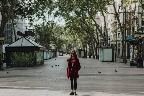 Full length portrait of woman standing on empty footpath in city, Barcelona, Spain - GMLF00179
