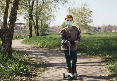 Portrait of boy wearing protective mask with kick scooter in a park - MOMF00863