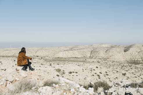 Full length of woman sitting on rocks while looking at desert landscape against clear blue sky - XLGF00125