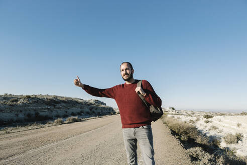 Man gesturing while hitchhiking on roadside at desert against clear blue sky - XLGF00128