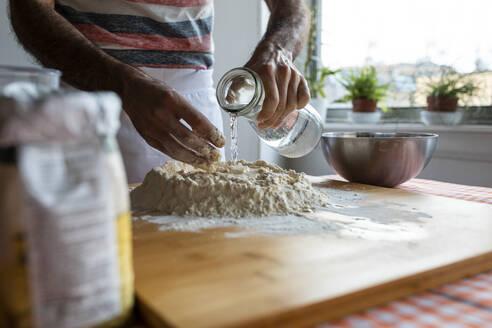 Crop view of man in kitchen preparing dough - WPEF02880