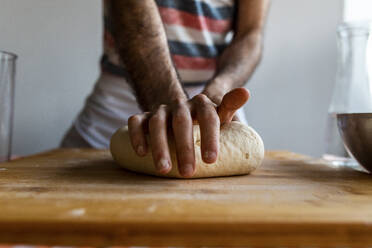 Man's hand kneading dough on wooden board, close-up - WPEF02886