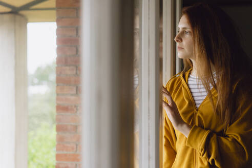 Pensive redheaded woman looking out of window - AFVF06212