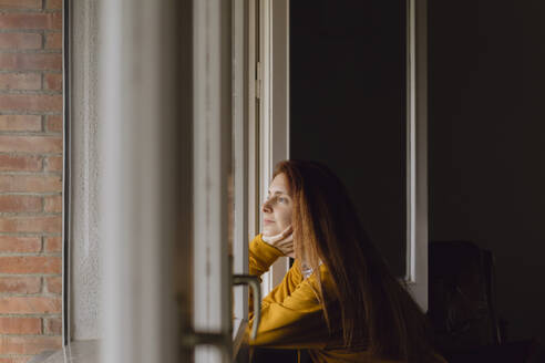 Redheaded woman at open window looking at distance - AFVF06215