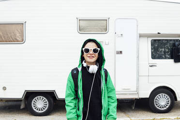 Portrait of boy with headphones wearing sunglasses standing in front of camper - JCMF00694