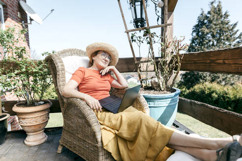 Portrait of pensive mature woman with laptop relaxing on terrace - KMKF01315