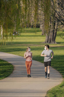 Couple wearing face masks while jogging on footpath at park - STDF00225