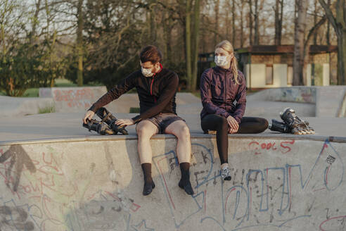 Young couple sitting with inline skates at skateboard park - STDF00234