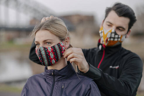 Young man adjusting face mask for woman while standing at park during COVID-19 - STDF00246