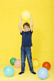 Full length portrait of smiling boy holding balloon against yellow background - JRFF04420