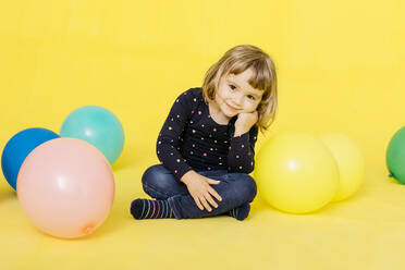 Portrait of smiling cute girl sitting with colorful balloons against yellow background - JRFF04423