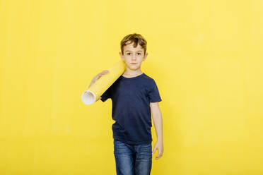 Portrait of cute carrying exercise mat while walking against yellow background - JRFF04426