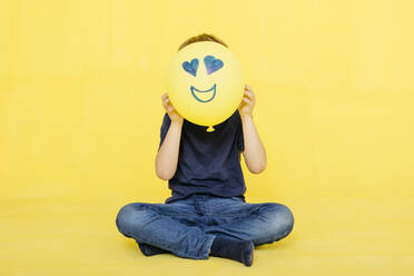 Boy holding yellow balloon with anthropomorphic face against colored background - JRFF04429