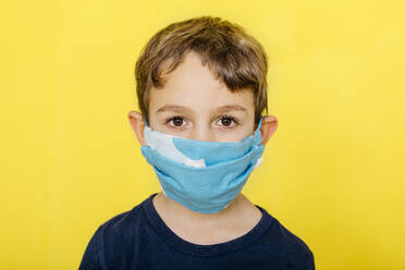 Close-up portrait of boy wearing face mask against yellow background - JRFF04432