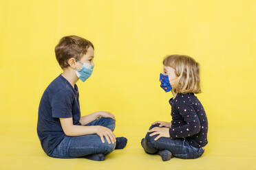 Full length side view of siblings wearing face masks while sitting against yellow background - JRFF04435